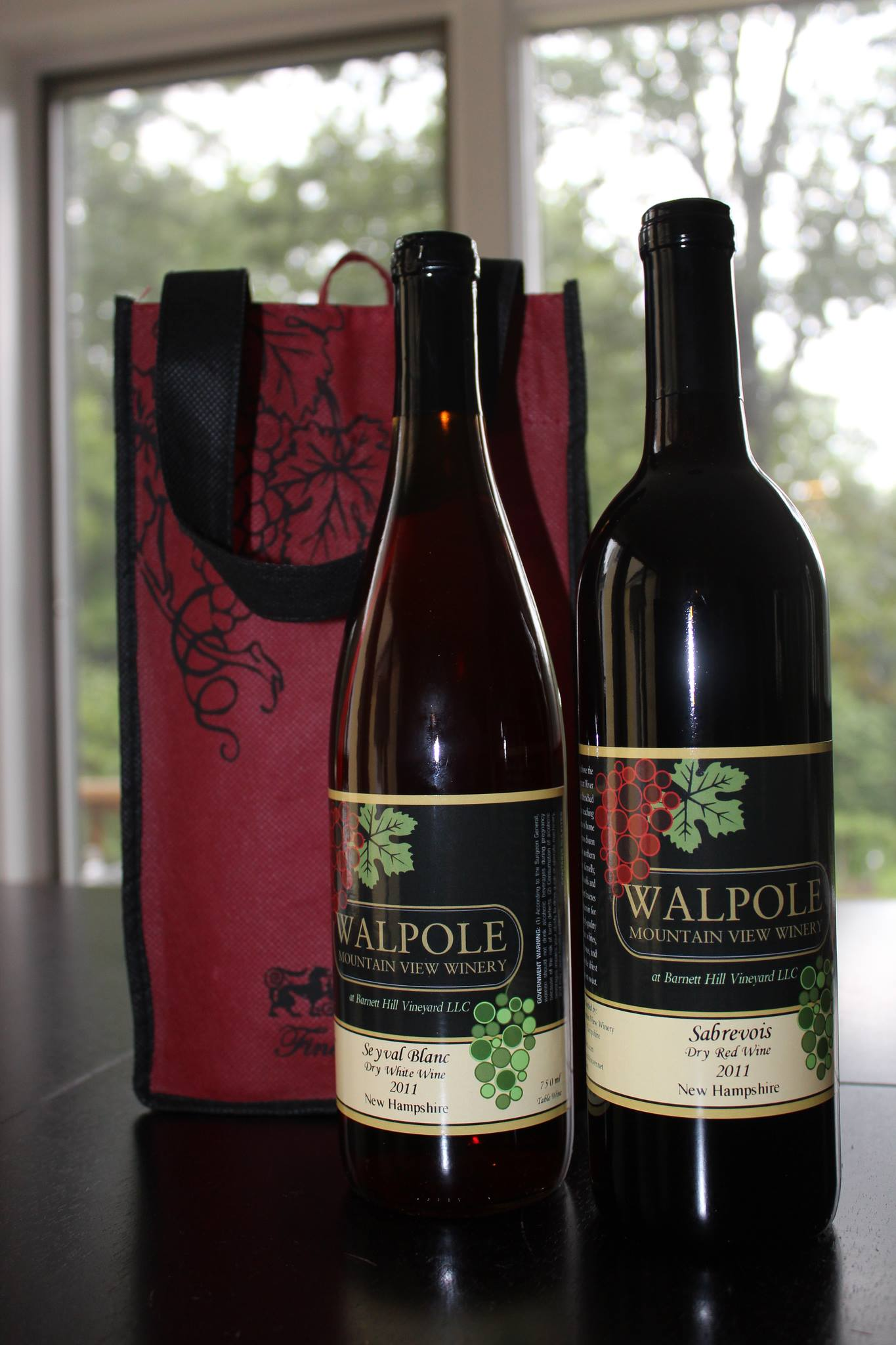two bottles of wine from Walpole Winery sit next to a red bag