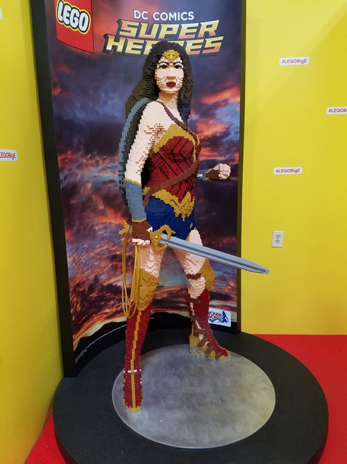 A lego sculpture of Wonder woman and her sword stands in the corner of an exhibit