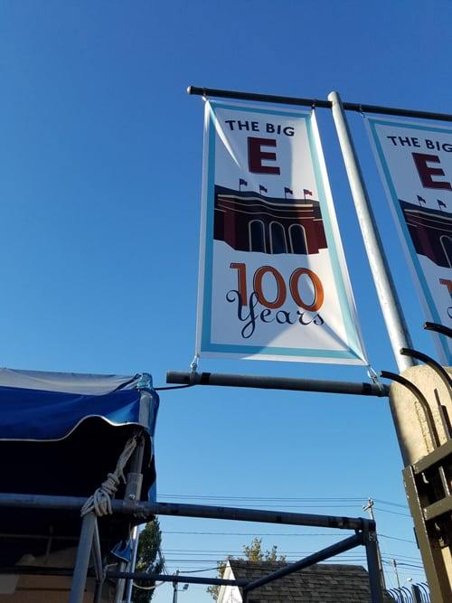 "Banners mounted on poles read ""the Big E 100 Years"""