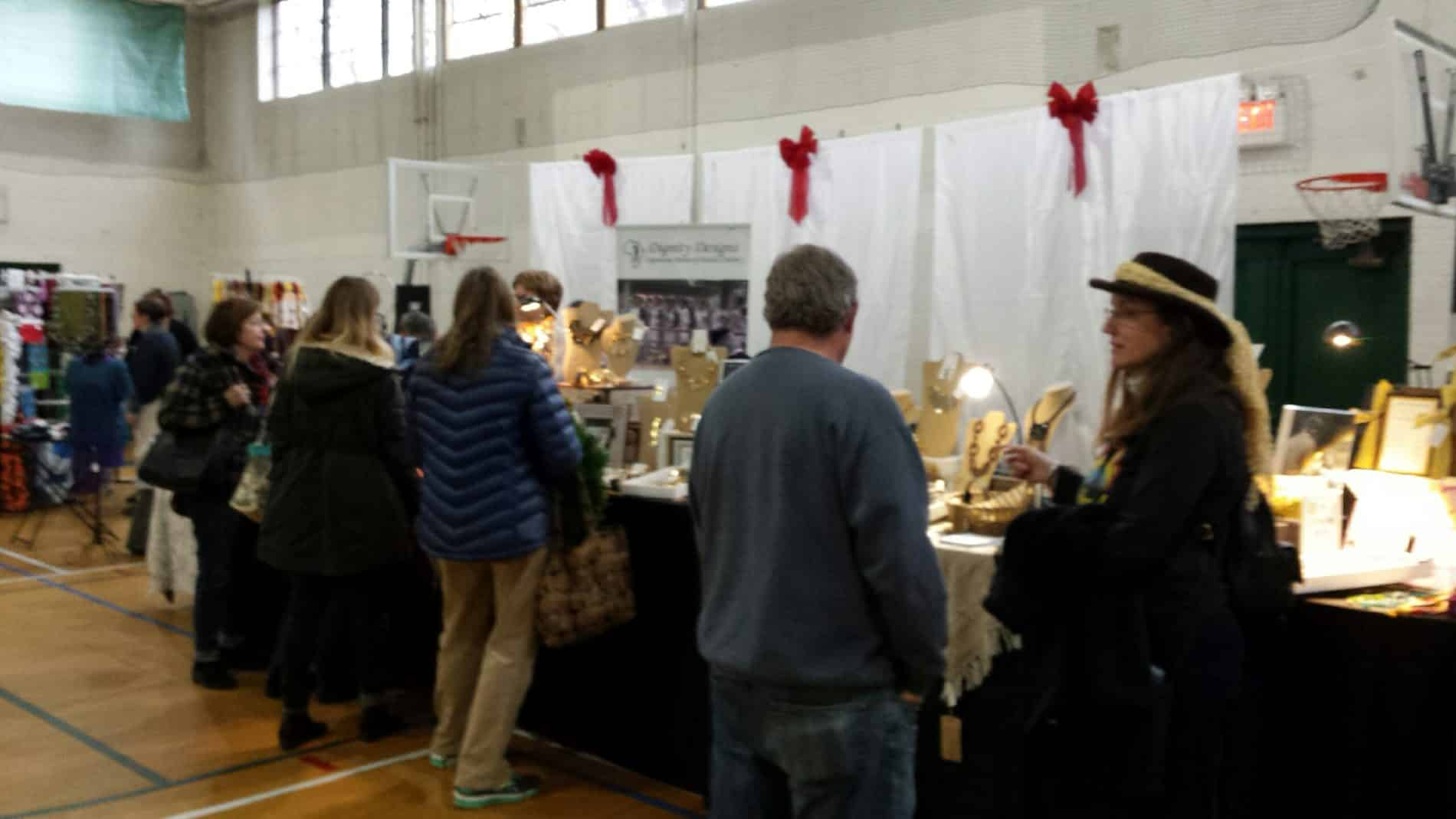 Several people walk through a craft fair looking at booths of peoples' wares in a gymnasium