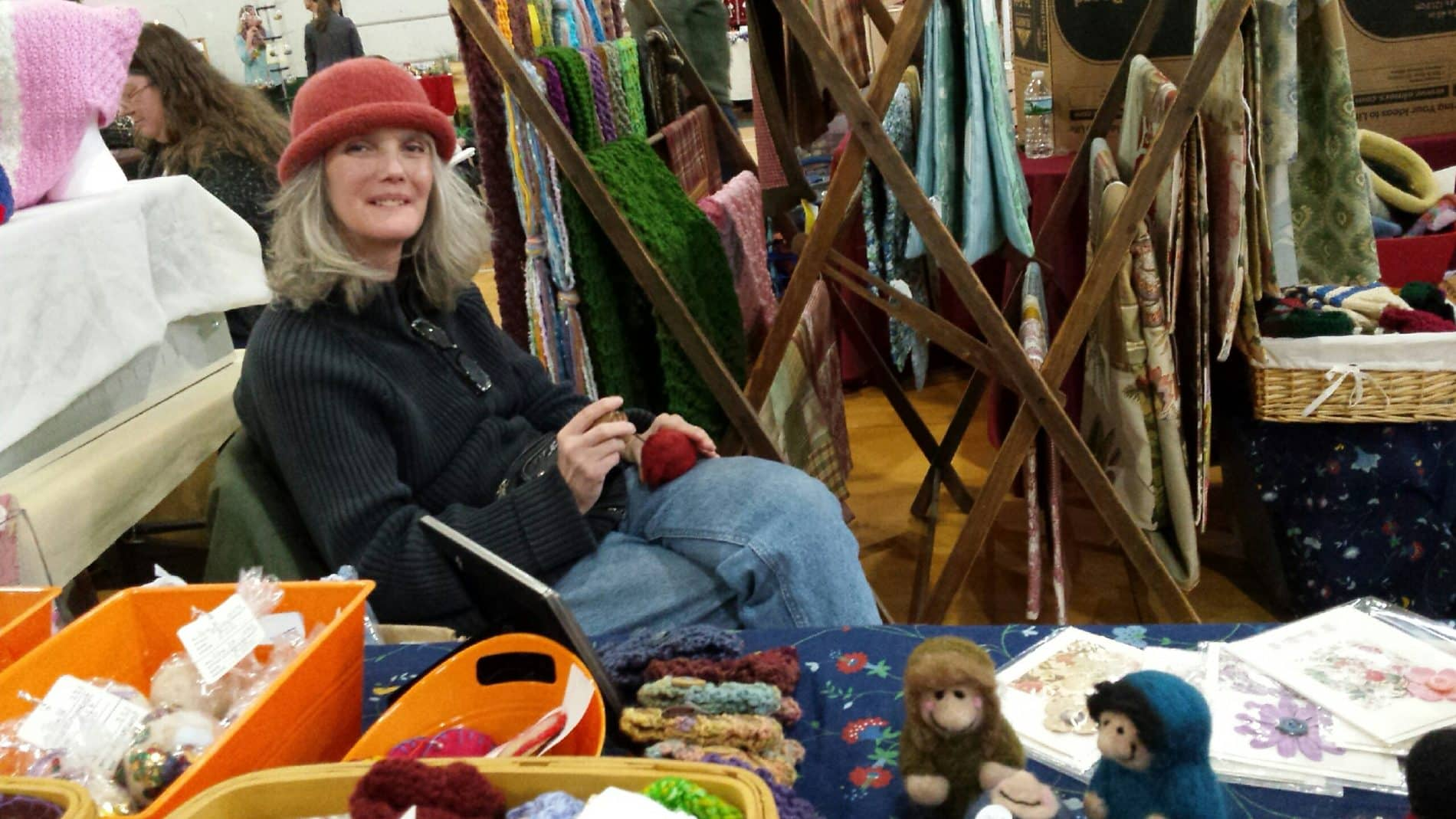 A crafter sits surrounded by her wares as she needle felts