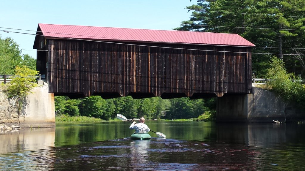 A covered bridge sits in the background while a kayaker paddles toward it to go underneath