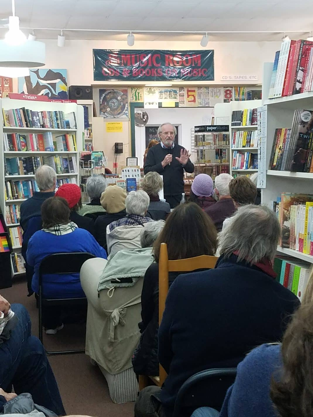 An author gives a reading at the bookstore in front of several guests. bookcases surround them