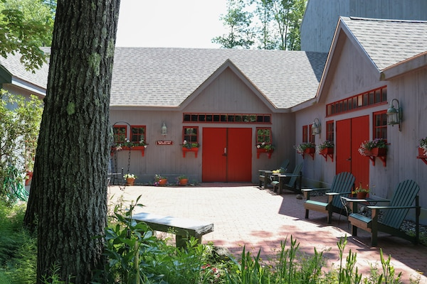 An old farmhouse converted into a theatre is painted gray, with red doors. A pathway leads from the foreground toward the threatre, while a tree trunk takes up the left half.