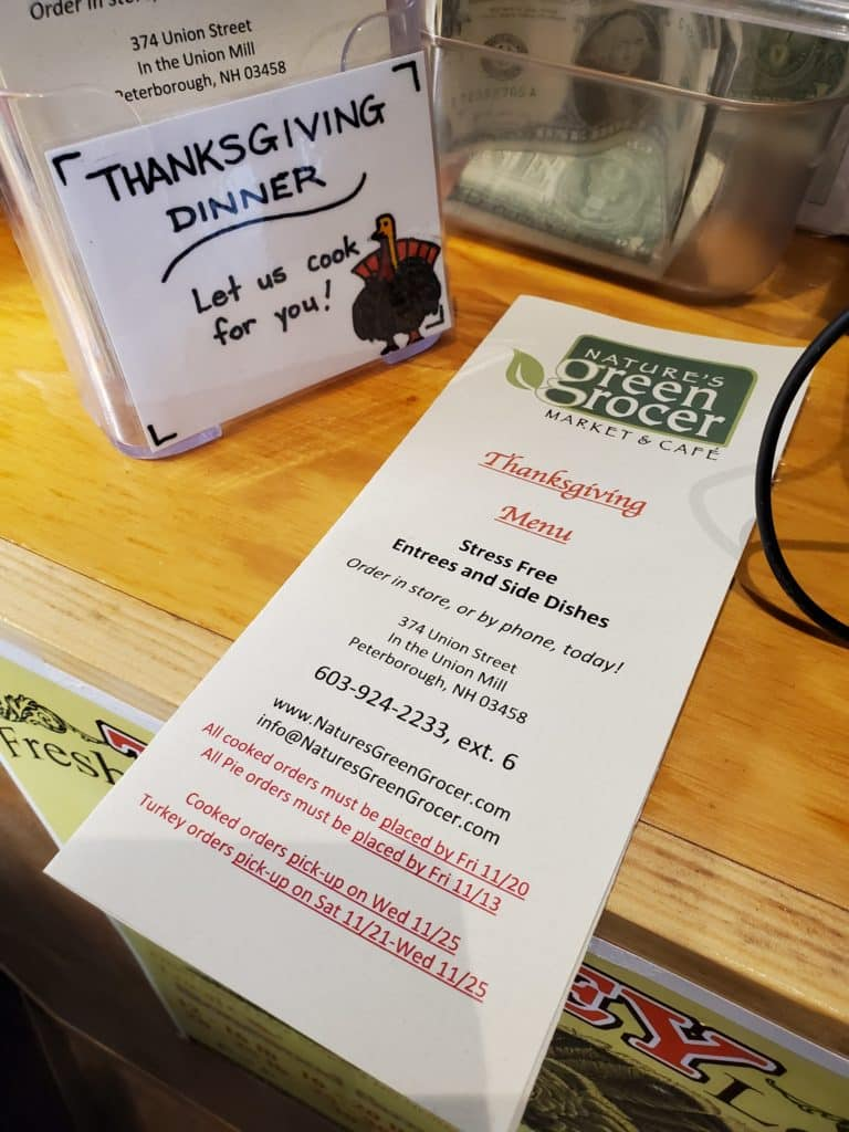 A folded menu of Thanksgiving dinner options at Green Grocer on a counter with a sign that reads 'let us cook for you!'