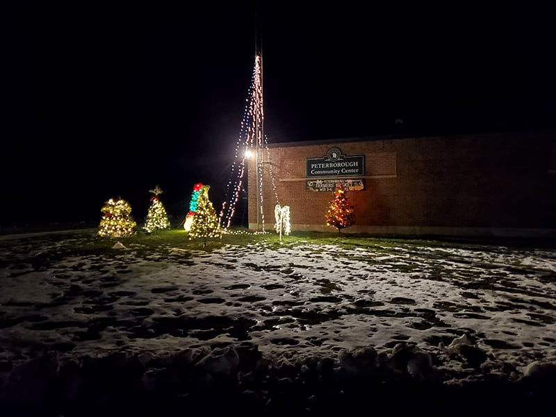 A brick building in the background with a sign that says 'Community Center'. In the foreground a pole with lights draped outward and several christmas trees are decorated.