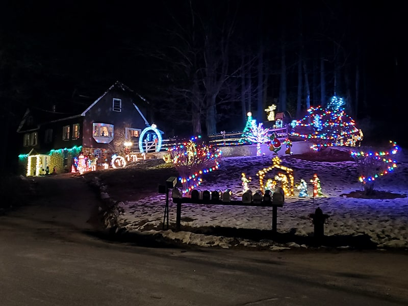 A house sits atop a hill surrounded by a wide display of christmas lights