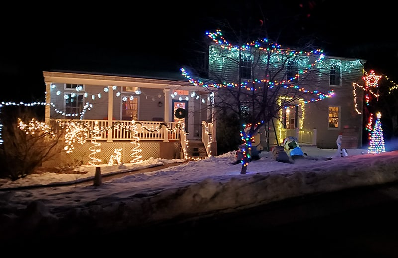 A house with lights made out of trees in the front of their deck. Snowflake lights hang from the trim, and a tree is decorated in multicolor lights