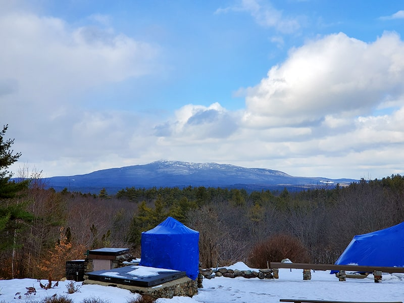 Mount Monadnock against a semi cloudy sky in the background while blue tents and stone benches are in the foreground