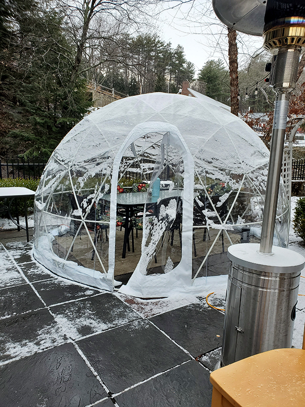 clear dome plastic igloo surrounds an outdoor dining table with snow nearby