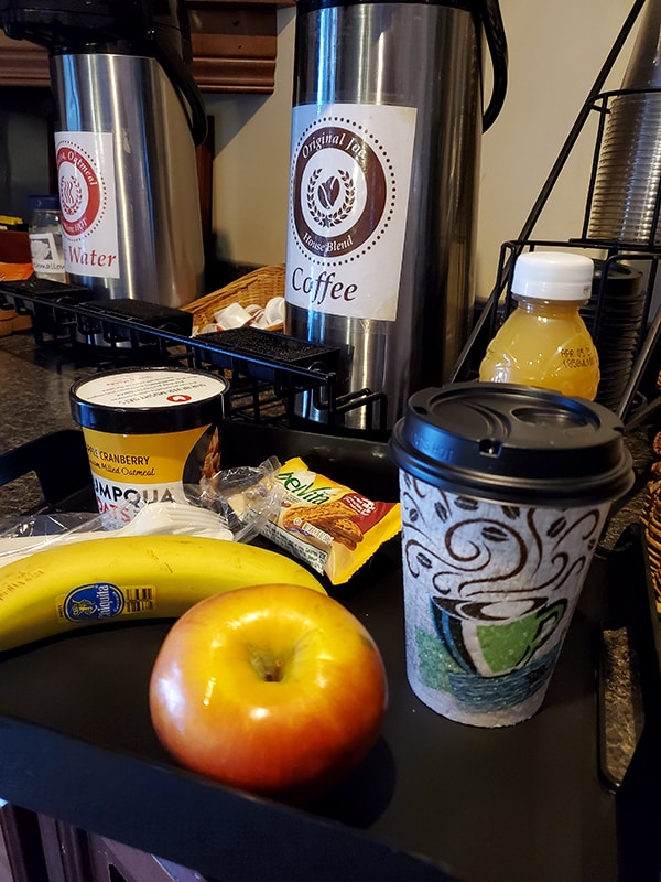A tray with fruit, juice, coffee and oatmeal sits in front of a coffee carafe