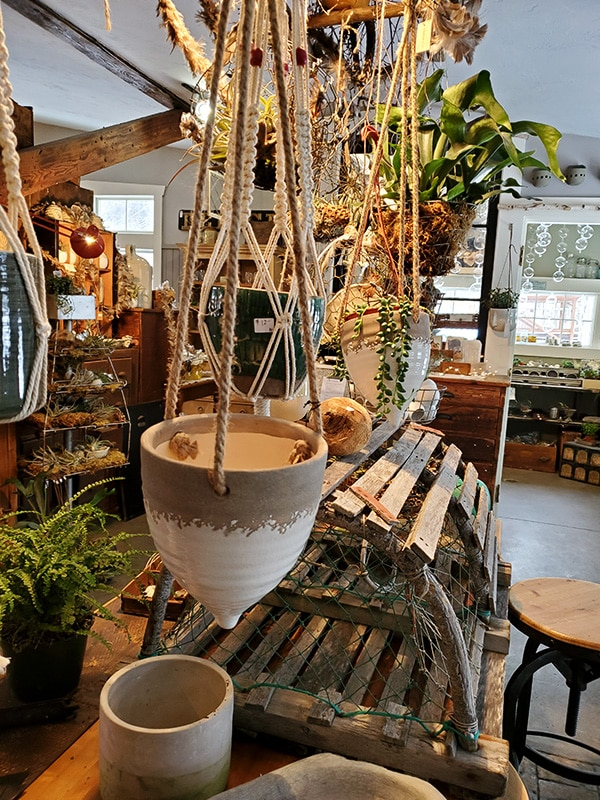 Several ceramic hanging pots hang above a table full of more pots