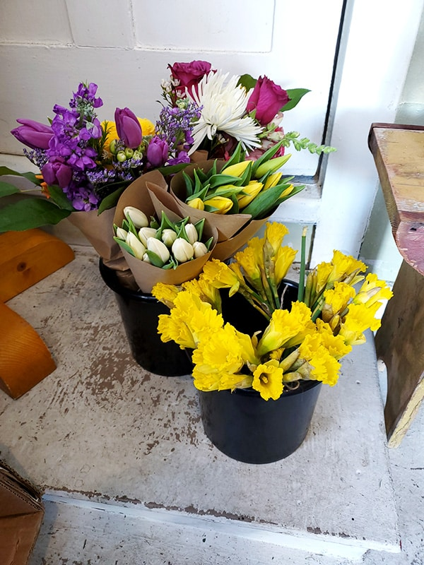 Two buckets with daffodils and grab and go bouquets.