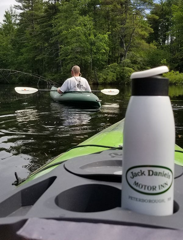 A white water bottle with the Jack Daniels Inn logo sits in a cupholder on a kayak in the foreground. In the background a man paddles out in his own kayak in the water