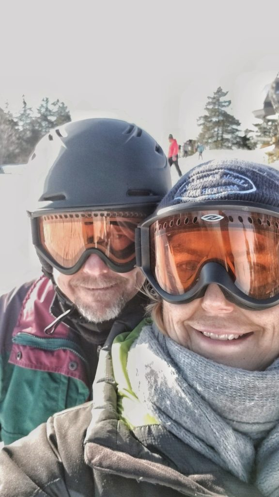 Two skiers with ski masks pose and smile for a photo while out on a trail