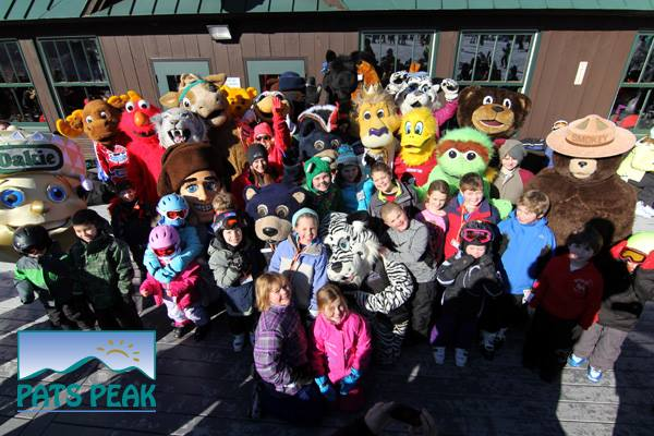 Various mascots and costumed people stand around with skiers