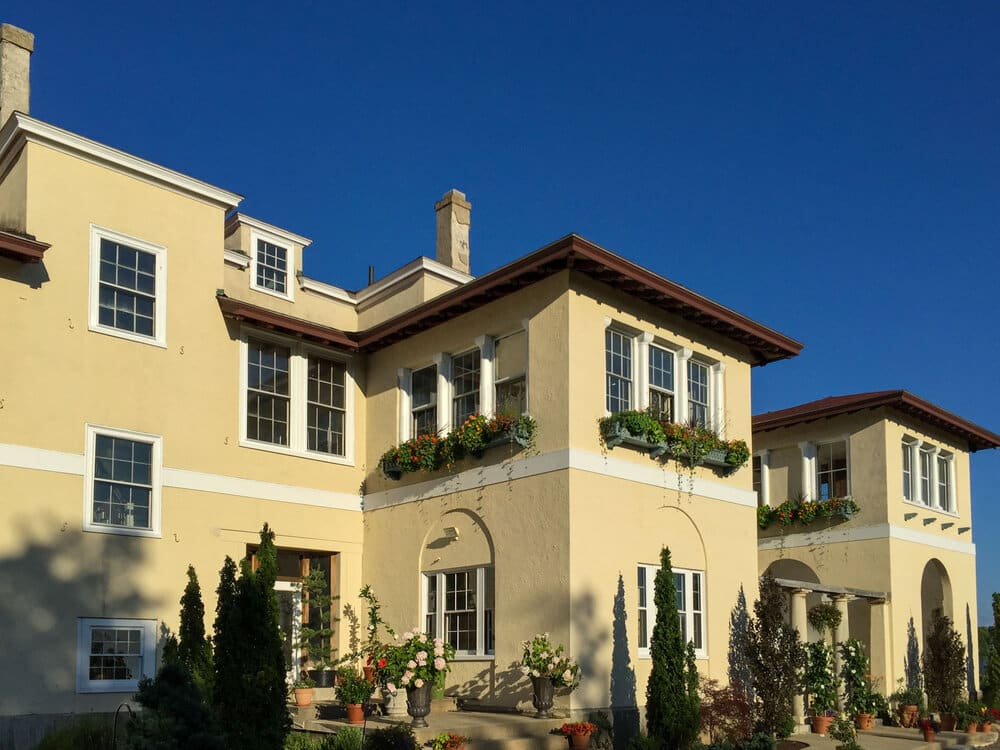 A light cream colored Tuscan-inspired mansion on a sunny day, with hedges and gardens surrounding the front.