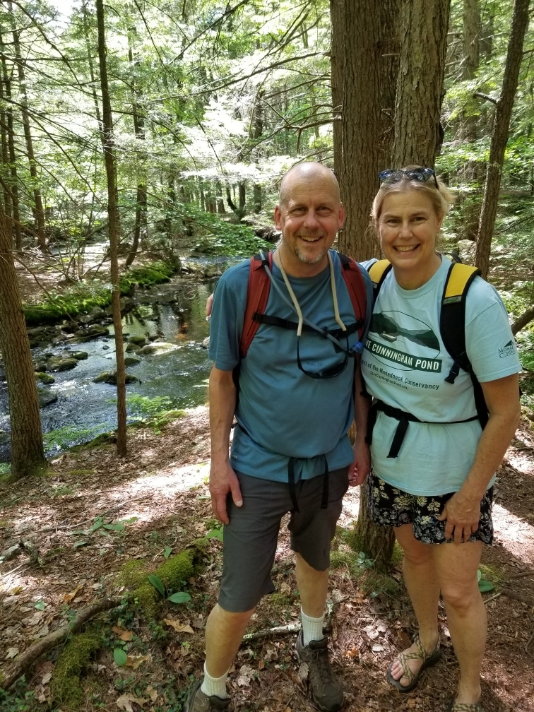 Man and woman stand in the foreground with a small brook behind them while hiking