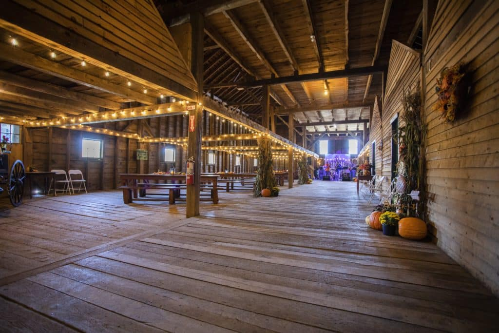Interior of a barn that has been converted. Bulb twinkle lights hang above low beams on the left where tables are arranged, while the far end has large windows overlooking the inside.