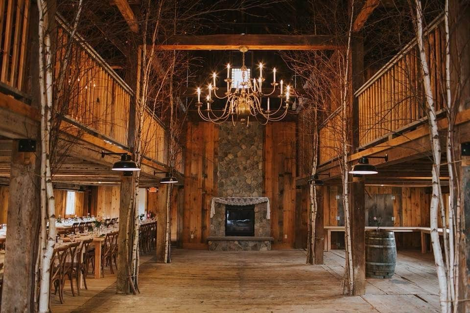 Interior of a wooden barn's middle aisle. Rows of bench seats and tables on either side, a chandelier above, and a stone fireplace in the center back.