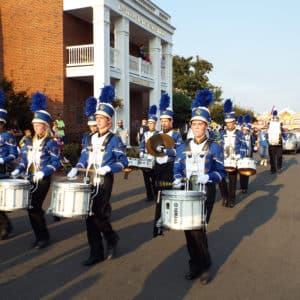 Drummers and other band members in blue and white uniforms march in formation