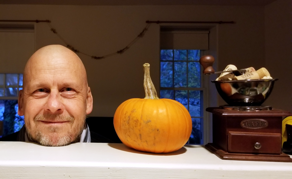 Man perches chin on a counter to the left of a small pumpkin while smiling