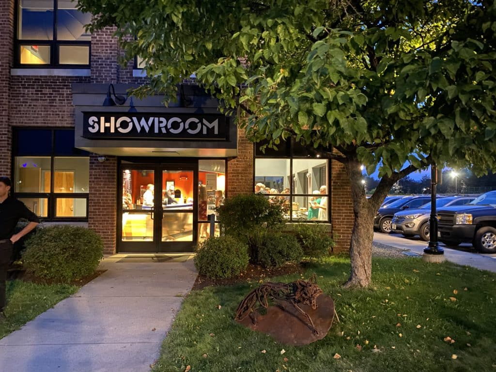 A grass lined path leads up to a brightly lit building with the name SHOWROOM above the doorway.