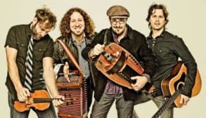 Four musicians holding different instruments while grinning at the camera.