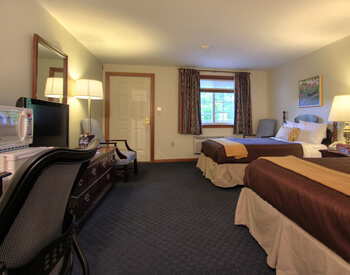 Spacious guest room with two double beds topped with java-colored spreads and gold throws