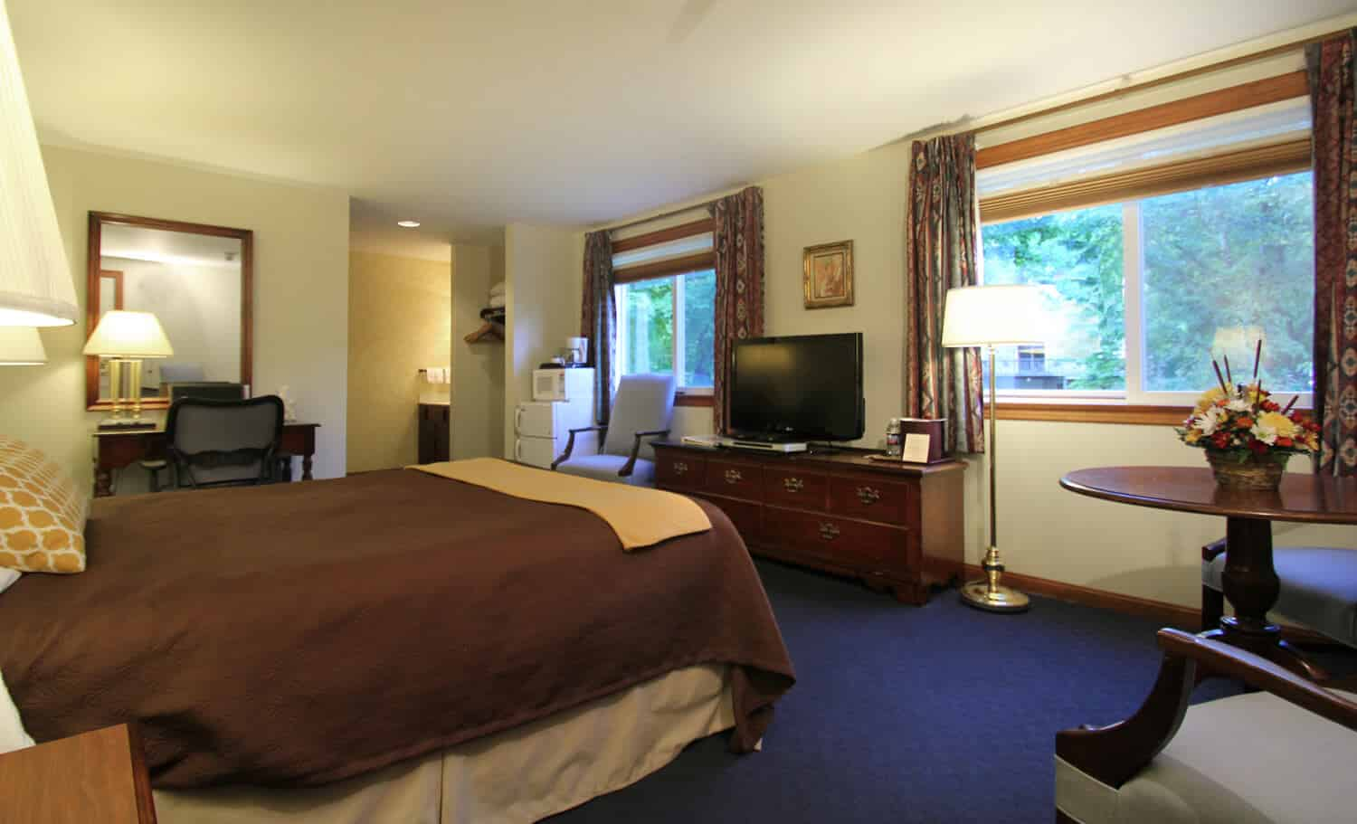King bedroom with a view overlooking the river features a large table to sit at and a flatscreen TV