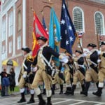 Eight men in Revolutionary War uniforms and tri-corner hats march in a downtown parade