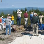A group of bird watchers stand watch for migrating hawks with binoculars, scopes, and cameras