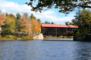 covered bridge over a lake with fall foliage surrounding it