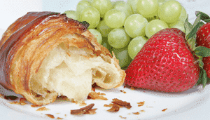 A flaky croissant, strawberries and grape sit on a plate