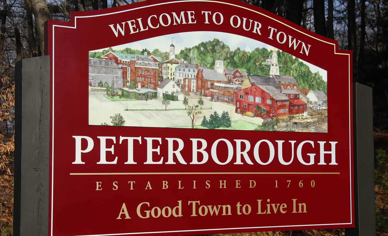 A red sign with a watercolor image of downtown Peterborough greets drivers as they enter town lines