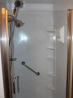 Interior image of walk-in shower with corner shelving, a grip bar and showerhead