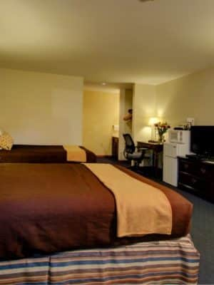 Spacious guest room furnished with two double beds, refrigerator/freezer and flat screen tv