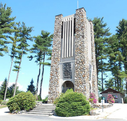 A stone tower surrounded by pine trees