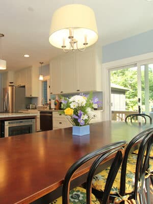 Table with seating for eight in modern kitchen and sliding glass door to sunny deck
