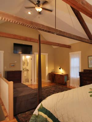 Spacious and bright master bedroom with exposed wood ceiling beams