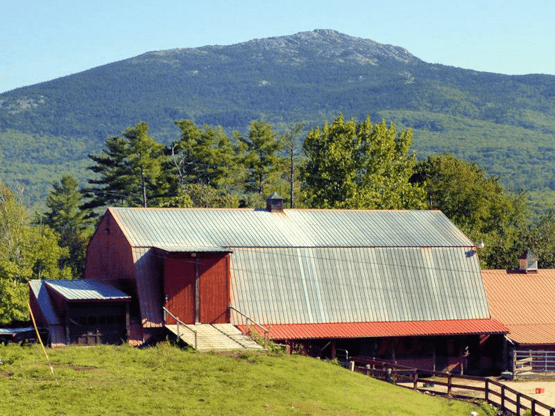A barn with a mountain behind it on a sunny day