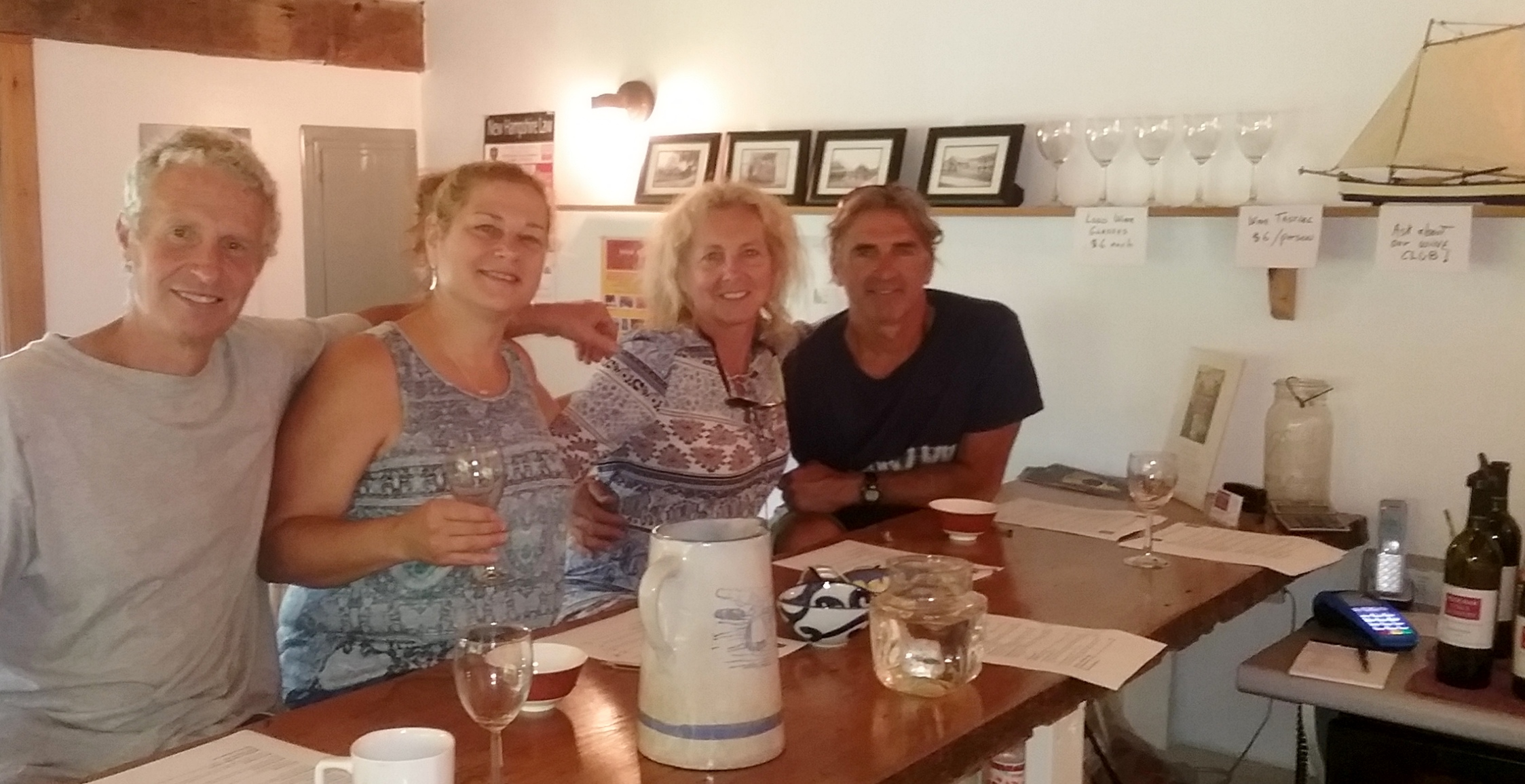 four people sit at a counter with wine glasses and smile at the camera