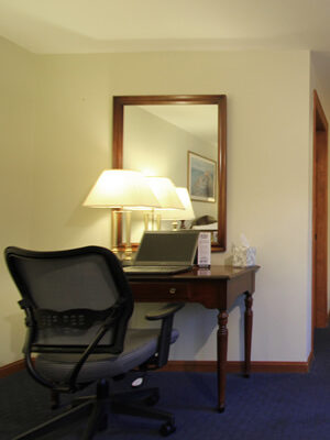 Guest room view towards vanity area featuring royal blue carpet, desk with adjustable chair, refrigerator, and upholstered chair