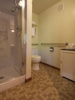 Tile-floored bathroom with glass-doored walk in shower, commode, linen cabinet, and grab rails