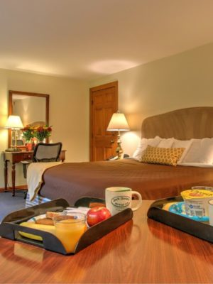 Large room with king bed, work desk and extra seating with breakfast trays
