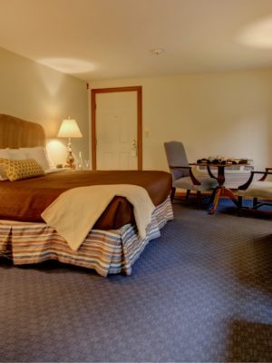 Spacious guest room with king bed with striped bed with royal blue carpet and cream walls