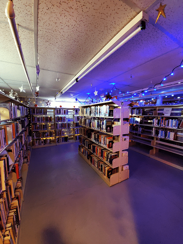 A dim room of library bookshelves with blue christmas lights on the ceiling