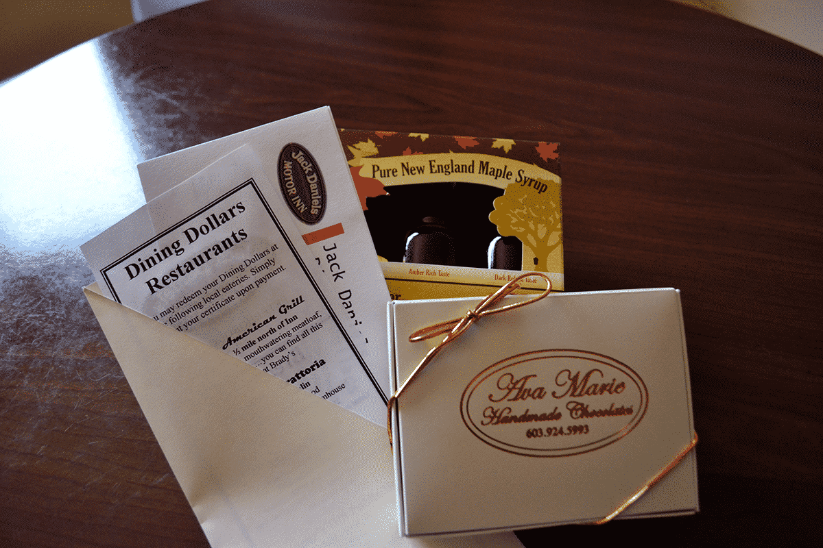 A box of chocolates, syrup samples and dining vouchers sit atop one another, then placed on a table