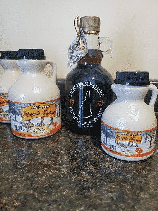 Various sizes of maple syrup jugs sit on a table, three of plastic and one of glass