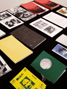 Multiple zines are lined up on a table for guests to flip through